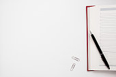 Blank notebook with pen and clips free space. Office supplies on empty white table, copy space for text or advertisement. Business, workplace, paperwork concept