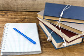 Blank notebook with pen, books earphone on wooden table