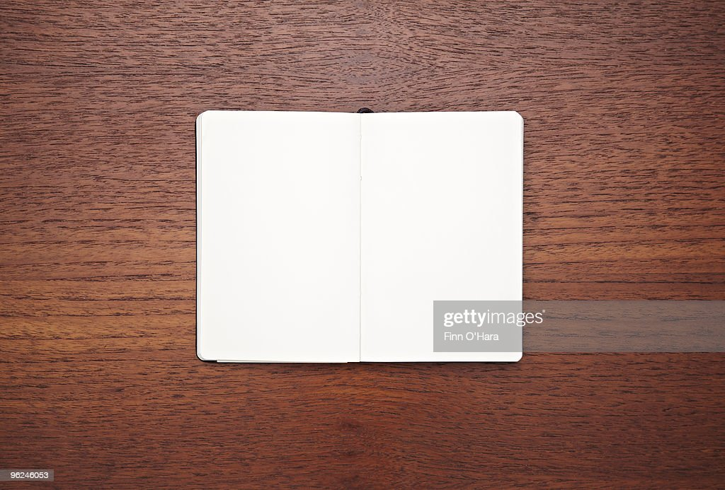 A blank, open white paged notebook on a table. : Foto stock