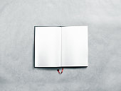 Blank opened book spread mock up with white pages. Reading empty paperback mockup. Black notebook inside template. Brochure design isolated on textured paper. Textbook spread with bookmark.