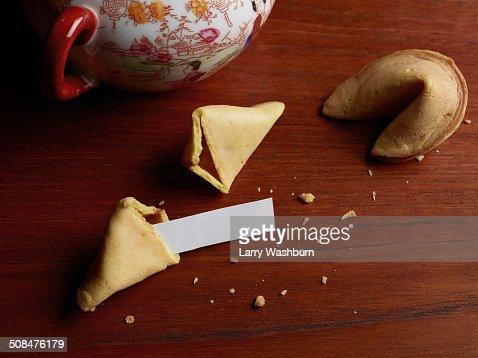 Blank paper in broken fortune cookie on wooden table