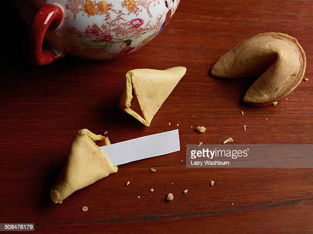 Blank paper in broken fortune cookie on wooden table