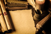 Blank parchment surrounded by books,scrolls and feather pen
