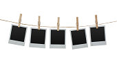 Five blank photos hanging on the clothesline isolated on white background with clipping path for the inside of the frames