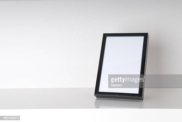 Blank picture frame on a white table with white background