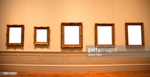 blank picture frames hanging on wall stock photo