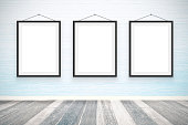 Blank picture frames on the wooden wall room