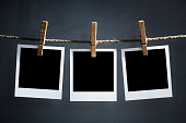 Blank instant print transfer polaroid photographs hanging on a clothesline