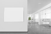Blank horizontal poster on the wall in bright office interior with clipping path around banner. 3d illustration