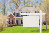 'Blank Real Estate Sign in Front of Beautiful New House - Ready for Your Own Text, Message or Logo.'