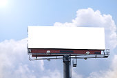Blank roadside billboard on a bright sunny blue sky day with area for your message, text and photos.