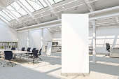 Blank roll up banner stand in loft office with clipping path around banner. 3d illustration