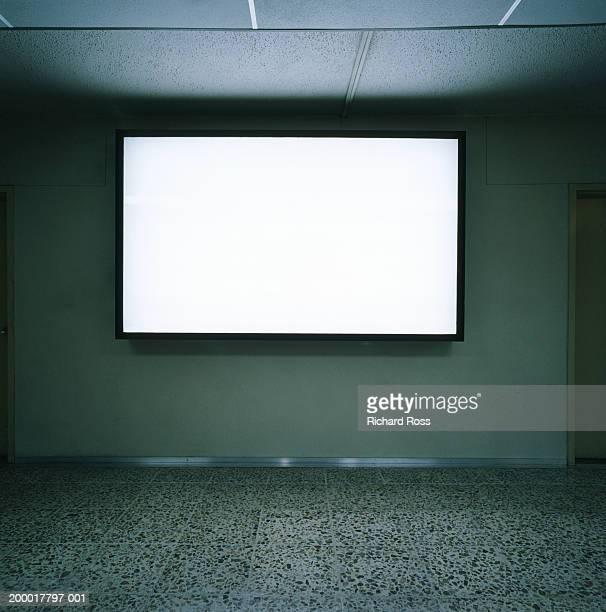 Blank screen on wall in empty room