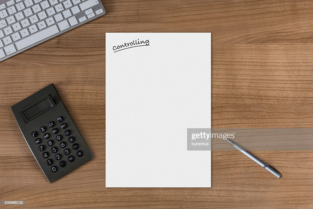 Blank sheet Controlling on a wooden table with calculator : Stock Photo