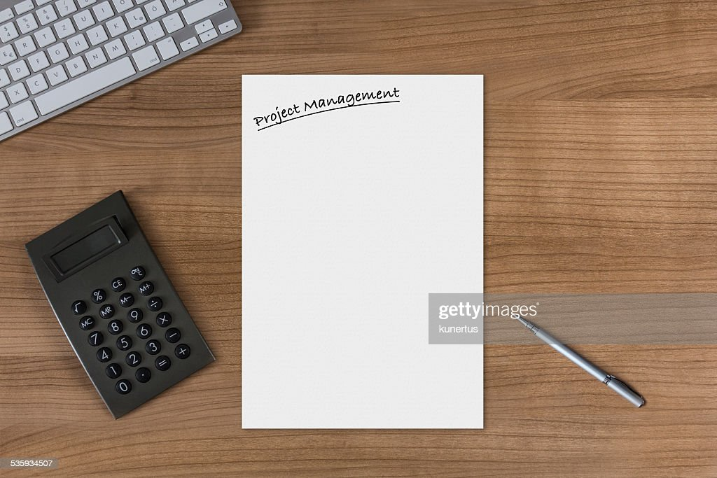 Blank sheet Project Management on a wooden table with calculator : Stock Photo