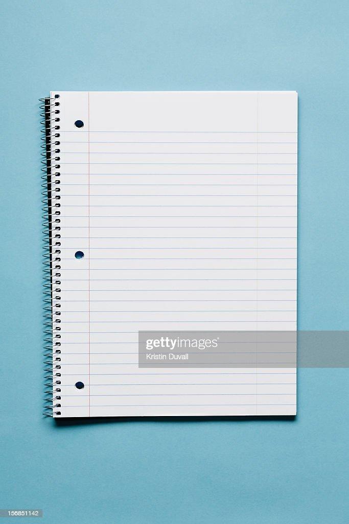 Blank spiral notebook on blue background