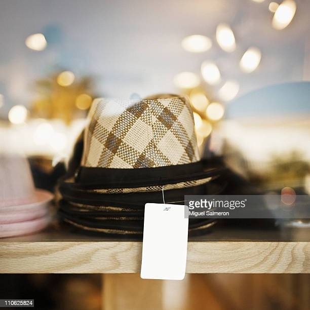 A blank tag on a stack of hats.