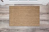 Blank tan colored coir doormat before the white door in the hall. Mat on wooden floor, product Mockup.