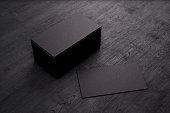 Blank template black Business Cards on black wooden background. 3D rendering