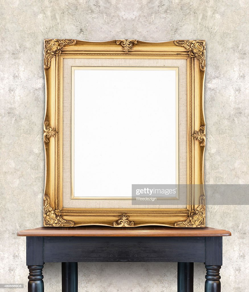 Blank vintage golden photo frame lean at light color concrete : Stock Photo