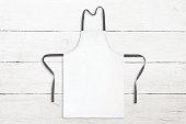 Blank white apron on white wooden background