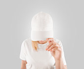 Blank white baseball cap mockup template, wear on women head, isolated, clipping path. Woman in clear hat and t shirt uniform mock up holding visor of caps. Cotton basebal cap design on delivery guy.