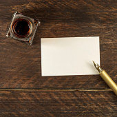 A square photo of a blank business card on a dark wooden background texture with a golden ink pen and ink bottle. A mockup or a banner with copy space