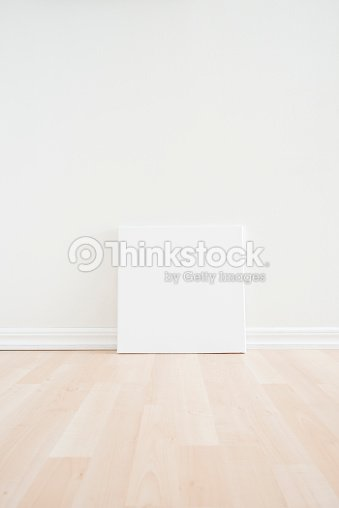 Blank White Canvas Against White Wall On Pale Wood Floor Stock Photo