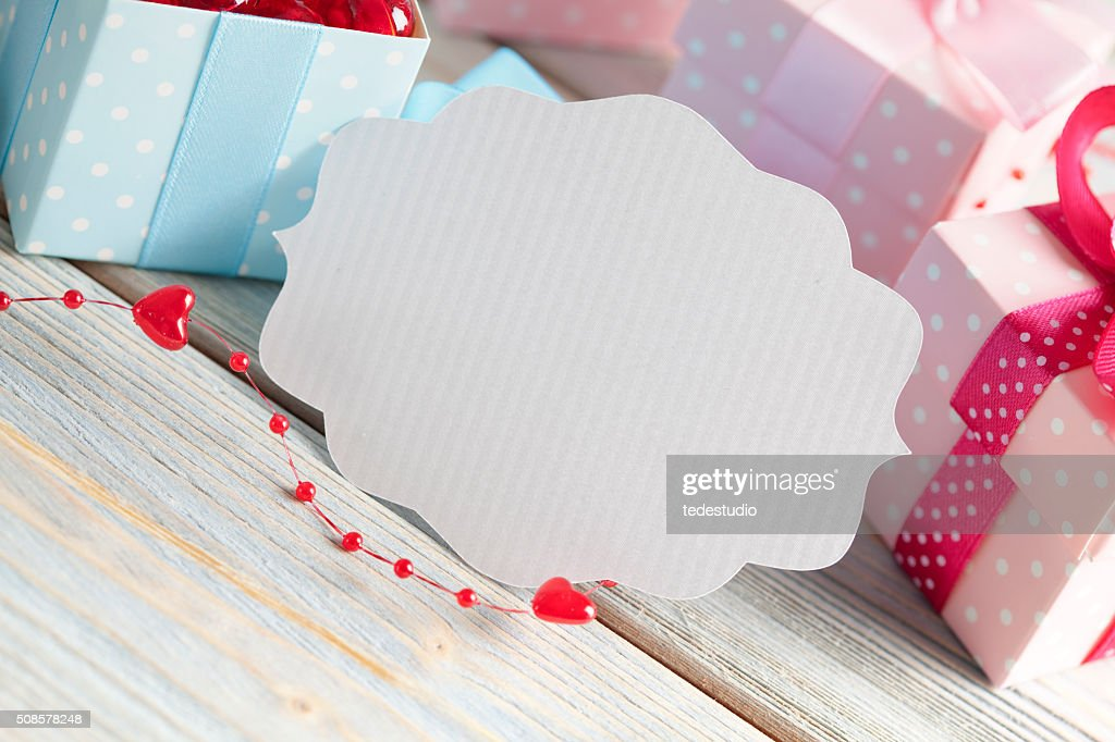 Blank white label and colored gift boxes : Stock Photo