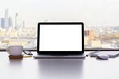 Front view of blank white laptop screen, coffee cup and other items on white desktop with sunlit city in the background. Mock up