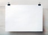 Blank white paper poster hanging on light wooden background. Blank template for placing your design. Front view.