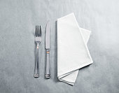 Blank white restaurant napkin mockup with knife and fork, isolated. Cutlery near clear textile towel mock up template. Cafe brand identity overlay surface for logo design.