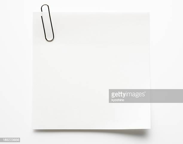 Blank white sticky note with paper clip on white background