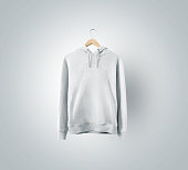 Blank white sweatchirt mockup hanging on wooden hanger. Empty sweat shirt mock up on rack isolated. Clear cotton hoody template. Plain textile hoodie design presentation. Loose overall casual jumper.