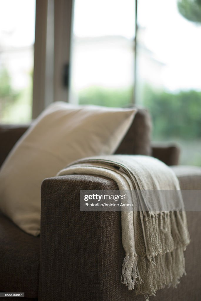 Blanket and cushion on sofa, cropped