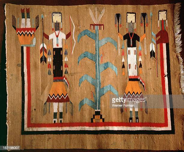 Blanket based on a sand painting design Two supernatural holy people flank the sacred maize plant which was their gift to mortals They are enclosed...