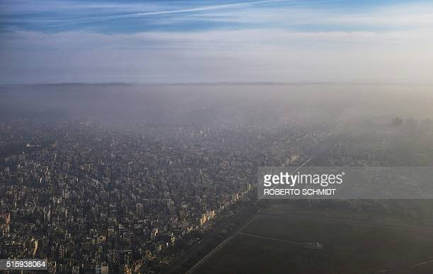 A blanket of smog extends over a densely populated neighborhood adjacent to the main airport in New Delhi on March 15 2016 Air pollution is a major...
