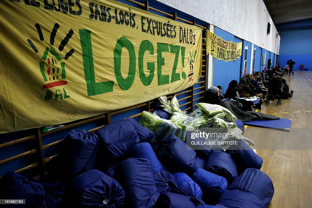Blankets and sleeping bags are piled in front of a banner that reads 'homeless, evicted, HOUSE THEM!' as some 200 people gathered by French association 'Droit au Logement' (DAL) occupy a municipal gymnasium on February 17, 2013 in Paris to demand that City Hall house them.