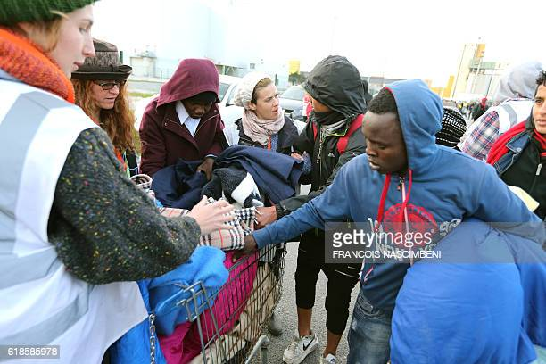 Blankets are distributed to migrants as they wait near the 'Jungle' migrant camp in Calais northern France on October 27 during a massive operation...