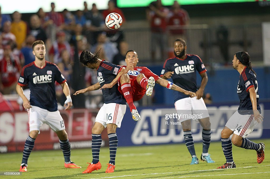 Blas Perez #7 of FC Dallas tries to kick the ball in midair from behind Daigo Kobayashi #16 of New England Revolution at Toyota Stadium on July 19, 2014 in Frisco, Texas.