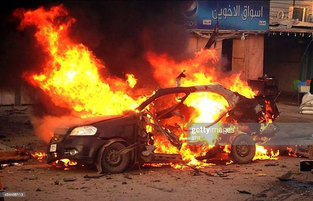 A blaze engulfs a car at the scene of an explosion in the Shiite Muslim AlAmin district of Baghdad on December 8 2013 A series of bombings which hit...
