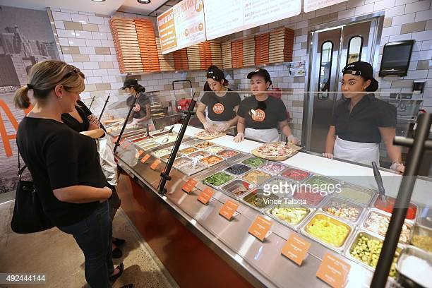 Blaze Pizza employees making customized pizza for customers at the Build Your Own Pizza counter at Blaze Pizza on Dundas St E at Yonge St in Toronto