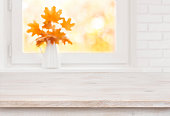 Bleached wooden table on the background of white autumn window sill