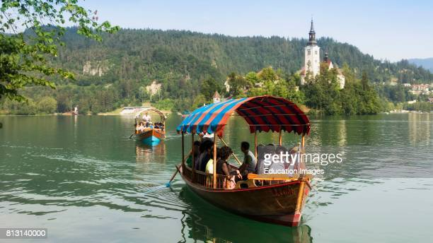 Bled Upper Carniola Slovenia Church of the Assumption on Bled Island Tourists enjoying boating excursion