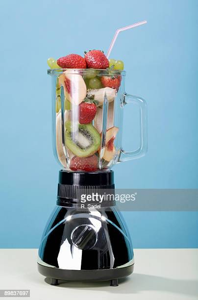A blender full of fruits with a drinking straw