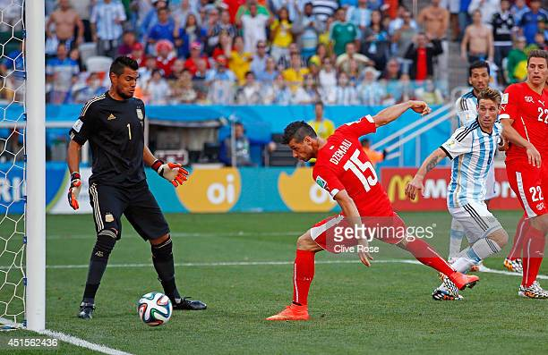 Blerim Dzemaili of Switzerland heads the ball toward goal and hits the post as Sergio Romero of Argentina looks on during the 2014 FIFA World Cup...