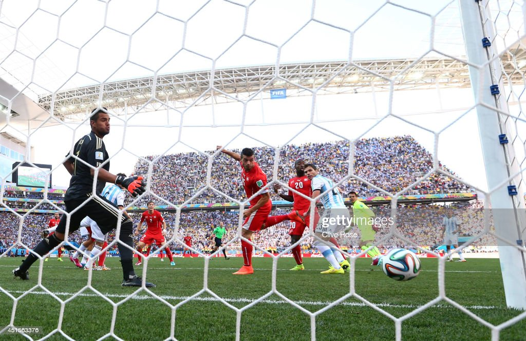 Blerim Dzemaili of Switzerland heads the ball toward goal and hits the post as <a gi-track='captionPersonalityLinkClicked' href=/galleries/search?phrase=Sergio+Romero&family=editorial&specificpeople=4100804 ng-click='$event.stopPropagation()'>Sergio Romero</a> of Argentina looks on during the 2014 FIFA World Cup Brazil Round of 16 match between Argentina and Switzerland at Arena de Sao Paulo on July 1, 2014 in Sao Paulo, Brazil.