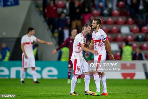 Blerim Dzemaili of Switzerland shares a laugh with Eren Derdiyok of Switzerland after the FIFA 2018 World Cup Qualifier between Latvia and...