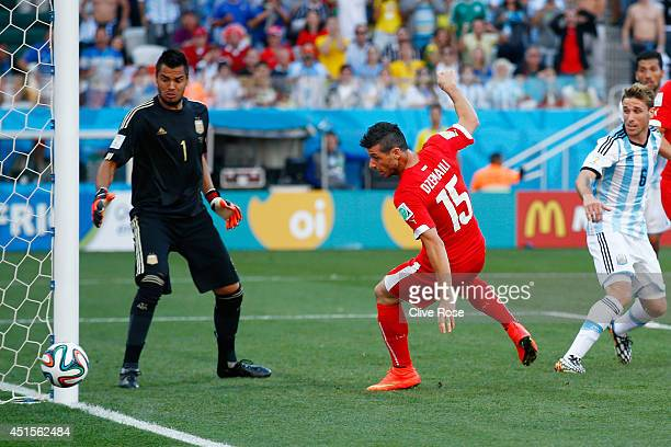 Blerim Dzemaili of Switzerland shoots the ball toward goal as Sergio Romero of Argentina looks on during the 2014 FIFA World Cup Brazil Round of 16...