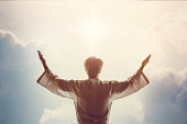 Man standing with arms wide open over bright sky